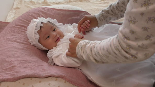 Cute baby model wearing a white lace baby dress.