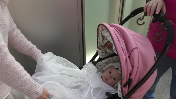 Cute baby model wearing a white lace baby dress. Go out riding on the pink stroller.