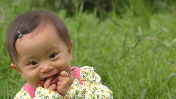 Baby is a happy mood in the spring of the field.